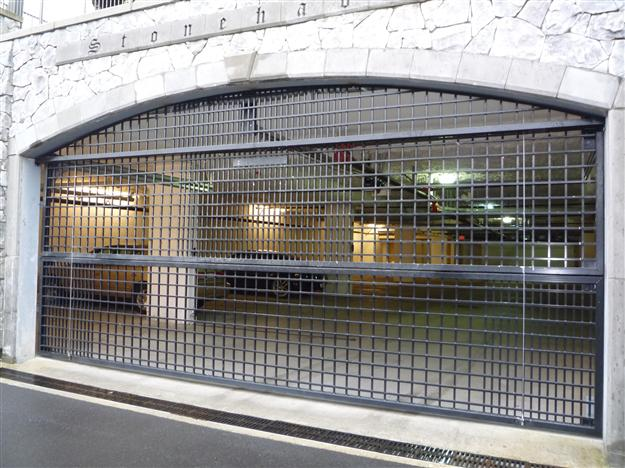 PD10- Two piece aluminum parkade gate with custom arched fascia to match opening