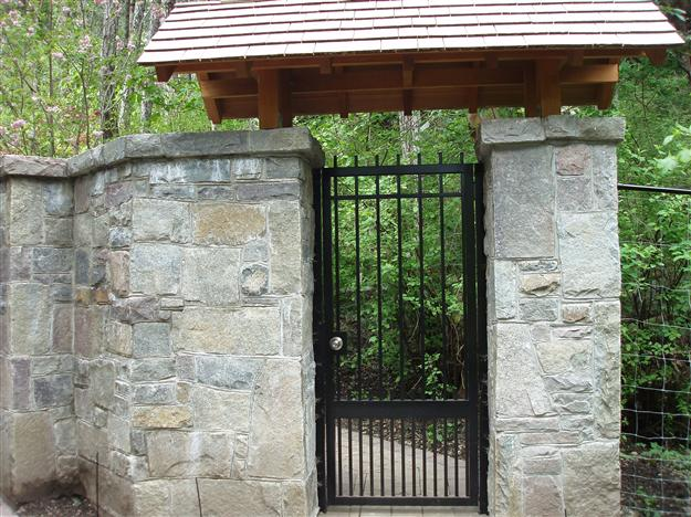 PG 04 Locking pedestrian gate to match double swing gate mounted on steel posts behind stone pillars