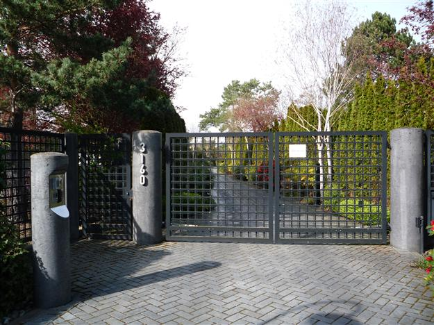 SWG 14 Custom aluminum gate design mounted on round concrete pillars with matching pillar for telephone entry